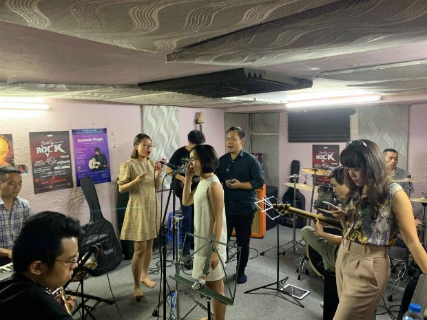 Hơn 15 người FIS tập hát trong một căn phòng nhỏ.