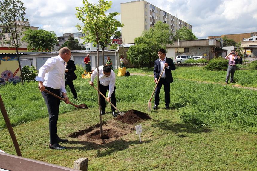 """Sau bữa trưa, Chủ tịch FPT Software Hoàng Nam Tiến và các lãnh đạo FPT Slovakia cùng các khách hàng đã trồng cây lưu niệm tại khuôn viên nhà Phần mềm ở Slovakia nhân dịp kỷ niệm 5 năm thành lập. """"Cây được chọn để trồng là ngân hạnh, lá cây hình trái tim, về mua thu sẽ có màu vàng lộng lẫy. Nơi trồng là sân chơi cho trẻ em ngay gần văn phòng FPT Software tại Kosice"""", Chủ tịch Hoàng Nam Tiến cho hay."""