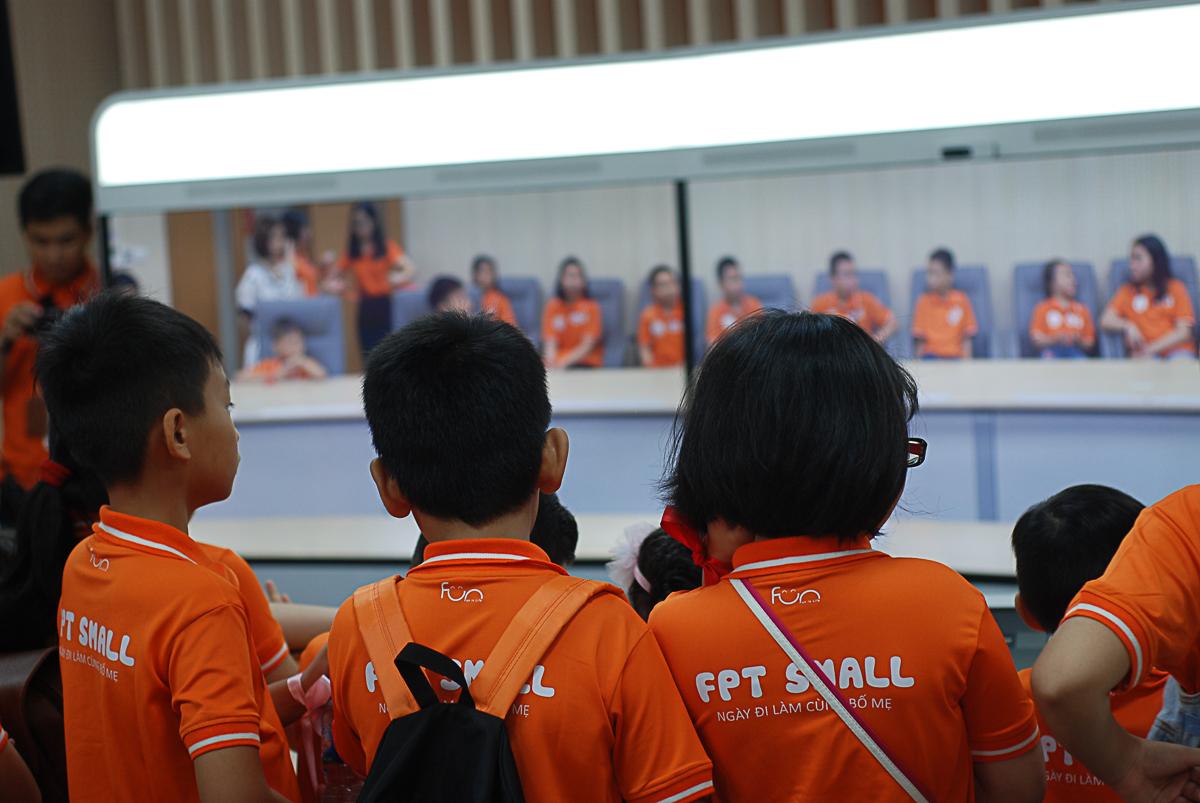 """Các bạn nhỏ ở 2 đầu cầu Hà Nội và TP HCM giao lưu quahệ thống Teleconference. Anh Phan Phước Nhựt -Trưởng phòng Văn hóa & Đoàn thể - nhắn nhủ đến các bé: """"Internet cho phép các con có thể nói chuyện với những người bạn và người thân ở xa, hay nước ngoài. Và các con hãy tự hào vì bố mẹ làm việc ở công ty cung cấp dịch vụ Internet hàng đầu Việt Nam""""."""