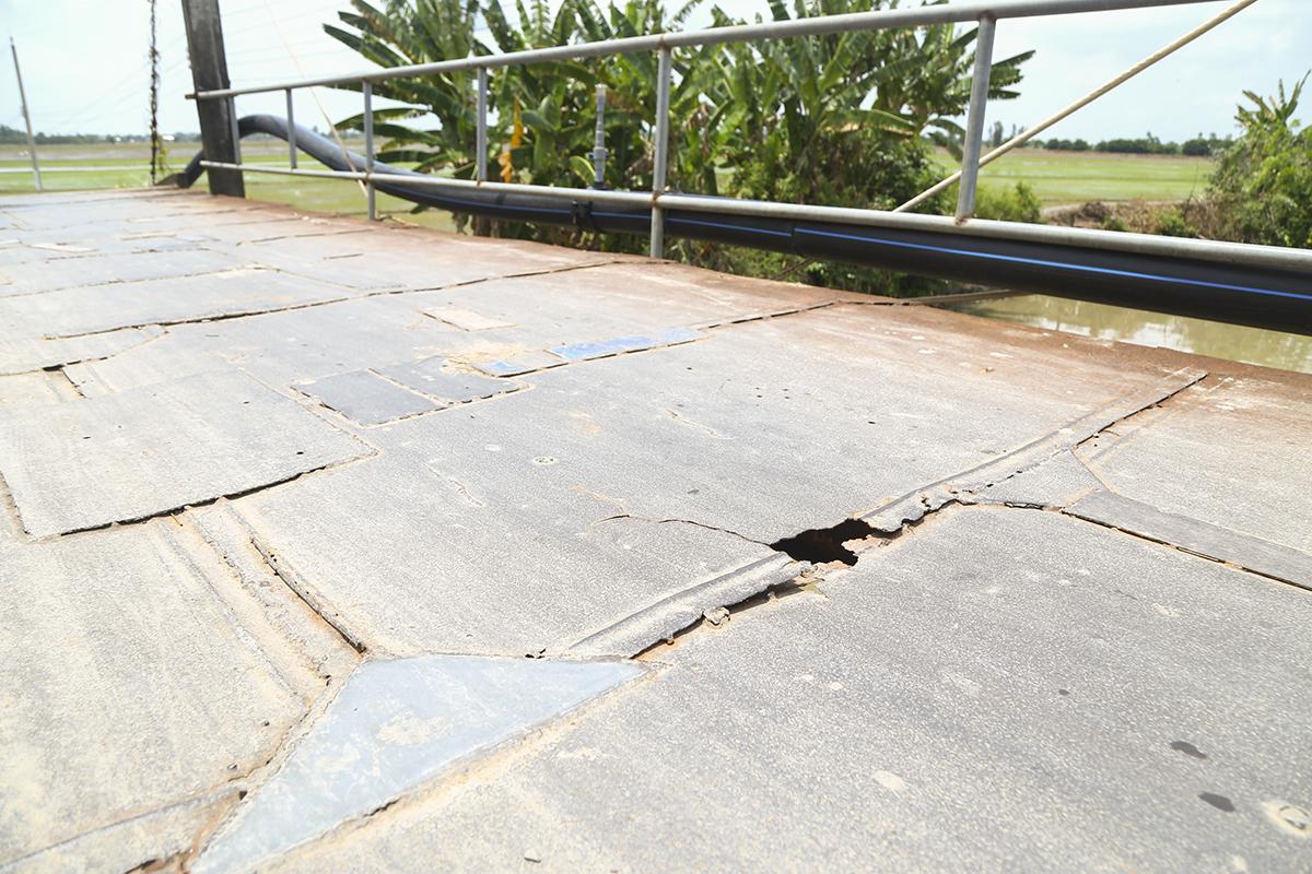 Những tấm vỉ sắt lợp nền cầu đã bong tróc và thủng lổ chỗ. Mỗi lần có xe máy chạy qua, nền cầu lại rung lên bần bật. Hai thành cầu chỉ được ngăn lại bằng những thanh sắt nhỏ đã hoen gỉ theo thời gian.