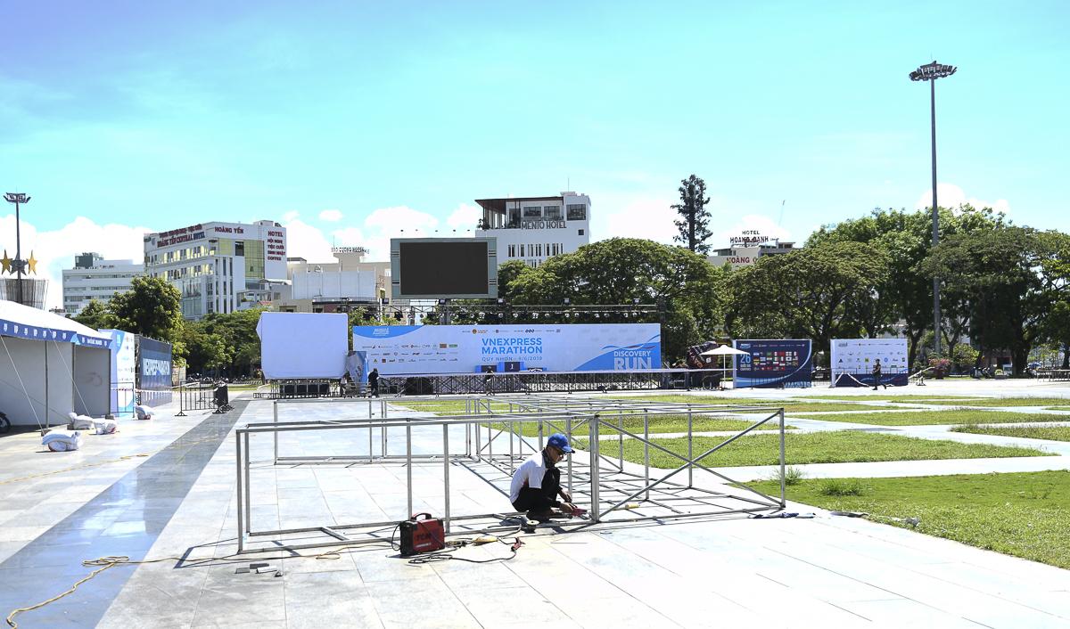 Nhiều ngày qua, hàng trăm công nhân dầm mình trong nắng nóng để lắp đặt sân khấu và các dãy nhà chuyên môn tại quảng trường Nguyễn Tất Thành, thành phố Quy Nhơn, Bình Định - nơi diễn ra các hoạt động chính của VnExpress Marathon 2019.