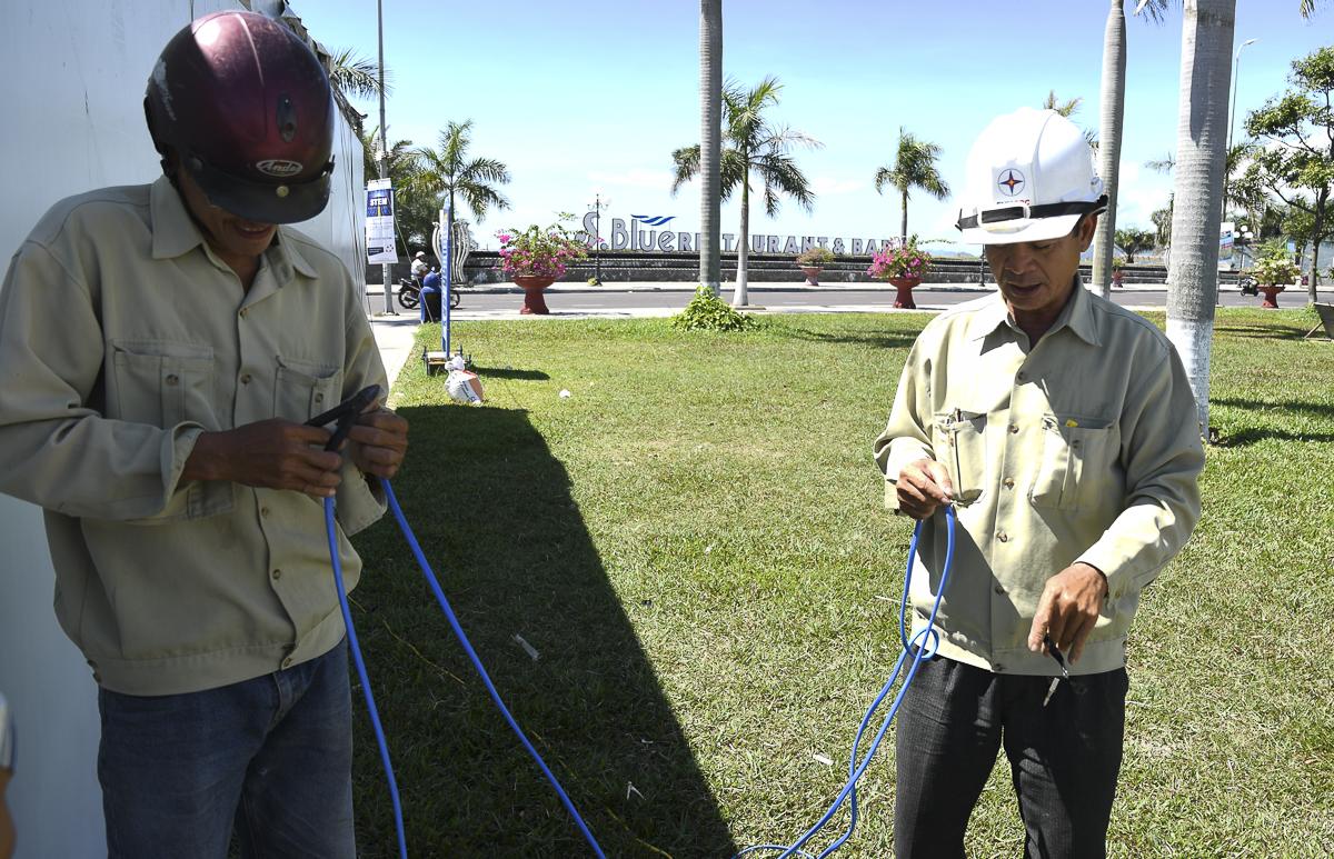 Các công nhân Công ty Chiếu sáng đô thị khẩn trương hoàn thiện việc kéo dây cấp điện cho sự kiện.