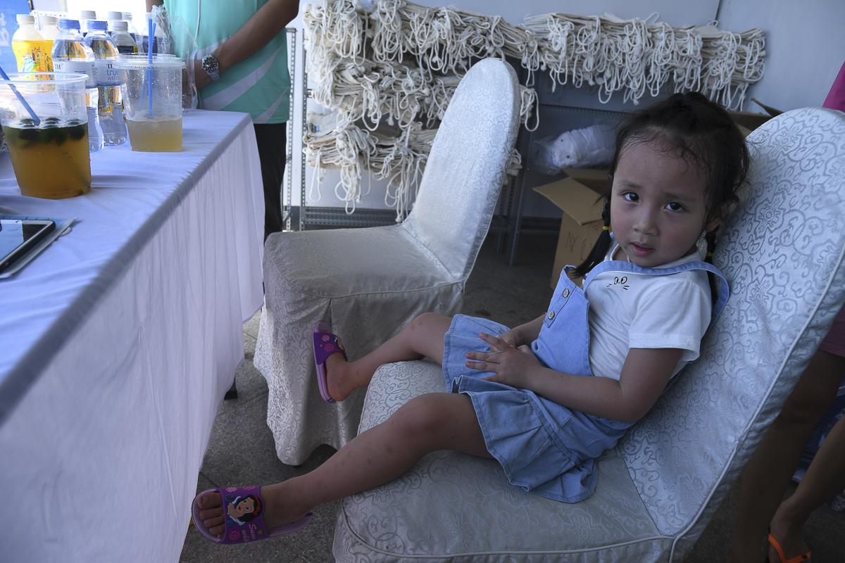 Một số gia đình kết hợp tham gia giải chạy và du lịch, đưa theo các bé nhỏ đến nhận số áo.