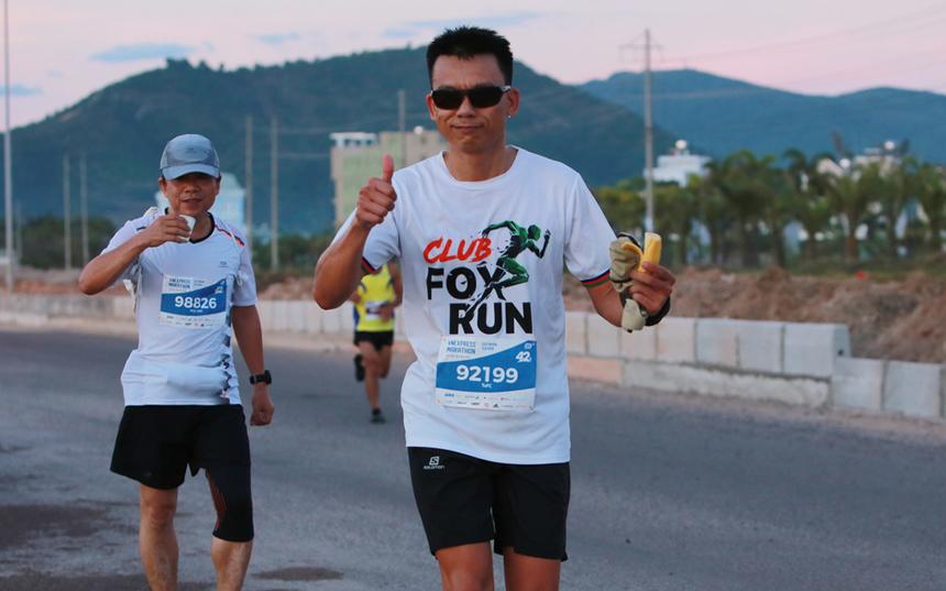 """Bình minh ngày mới, anh Phạm Công Tứ, Ban dự án Data Center FPT Telecom, ăn chuối sau khi uống nước tại một điểm tiếp tế bên kia cầu Thị Nại. """"Tôi muốn thử sức và vượt qua chính mình trên đường chạy đạt chuẩn quốc tế đầy thử thách này"""", anh Tứ chia sẻ về lý do lần đầu đăng ký mốc 42 km. Với người yêu chạy bộ, đỉnh cao chính là hoàn thành một cuộc đua marathon. Chỉ khi ấy,thành viên này mới được cộng đồng xác nhận mạnh mẽ, kiên trì, bền bỉ, lì lợm. Kết quả, anh Phạm Công Tứ chinh phục thành công và ghi danh vào nhóm 5% dân số thế giới chinh phục marathon."""