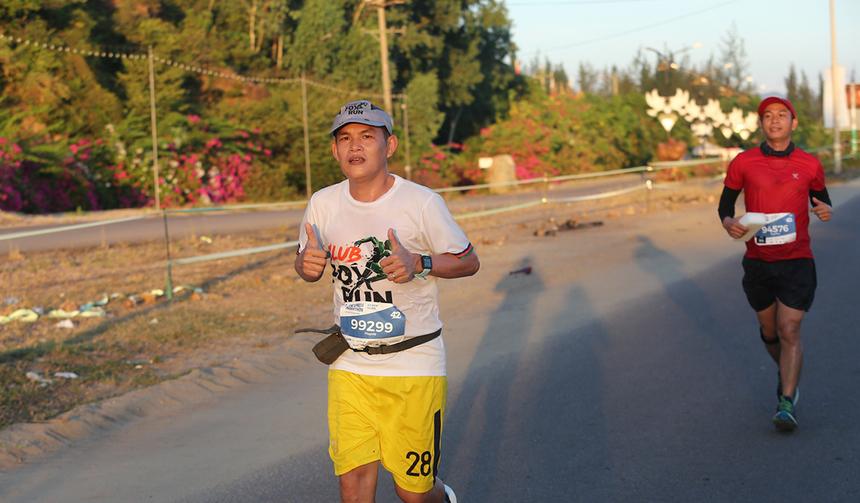 """Anh Võ Minh Pháp, Trung tâm Giám sát và Đảm bảo dịch vụ (SCC, FPT Telecom), đón bình minh ở bán đảo Phương Mai. Đây là lần thứ hai chạy full marathon của chàng trai SCC. Cách nay gần một năm, Pháp là một trong 7 người nhà 'Cáo' đã chinh phục cự ly 42 km tại Marathon Quốc tế Đà Nẵng (DNIM) với 5h45. """"Lần này tôi đặt mục tiêu rút ngắn 25 phút so với kỳ trước"""". Kết thúc chặng đua, anh Pháp hoàn thành hơn 5h, vượt kỳ vọng ban đầu. """"Cung đường biển Quy Nhơn rất đẹp và khoảnh khắc chạy trong bình minh ở biển miền Trung thật tuyệt"""", Pháp bật mí. """"Nhà tôi cũng gần nên chạy xong sẽ về Quảng Ngãi thăm gia đình""""."""