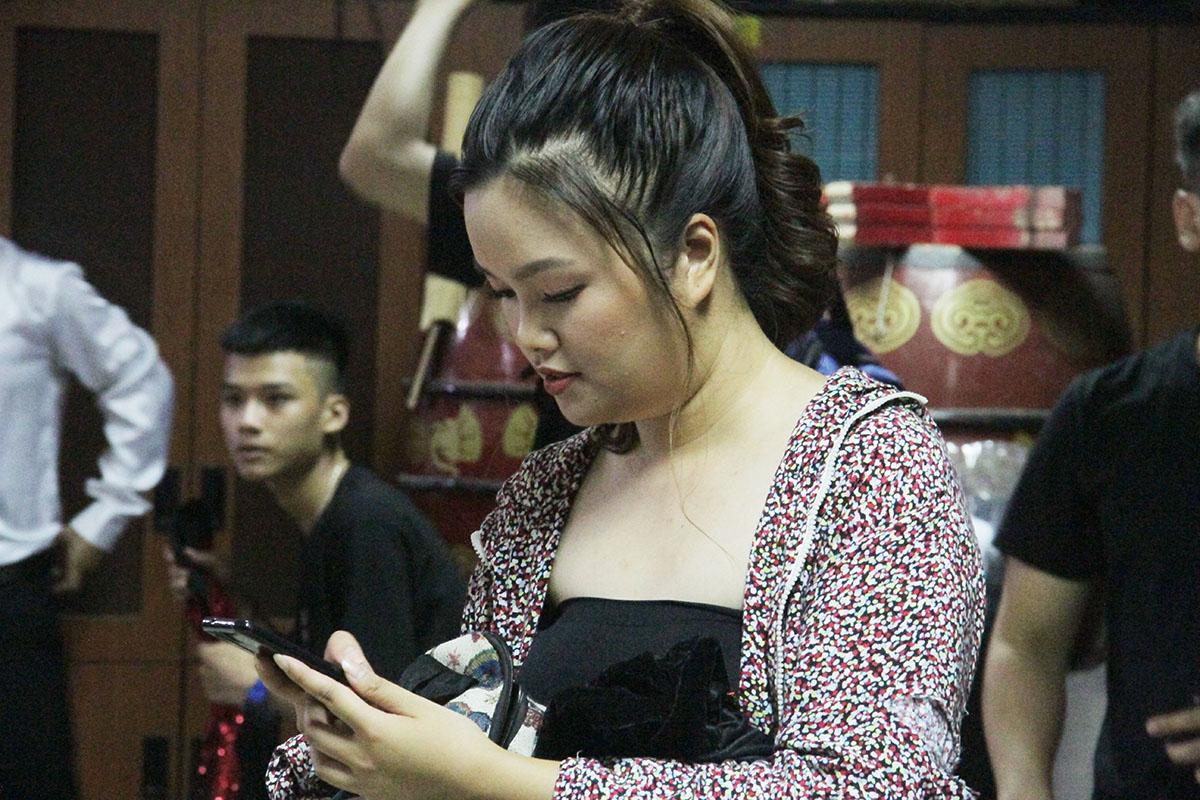 Dù lần thứ hai góp mặt với tư cách là diễn viên, nhưng chị Hồ Thị Nhật Tuyền, FPT Software, vẫn cảm thấy hồi hộp. Nữ nhân viên thường xuyên dùng điện thoại để trò chuyện với người thân trước khi lên sân khấu.