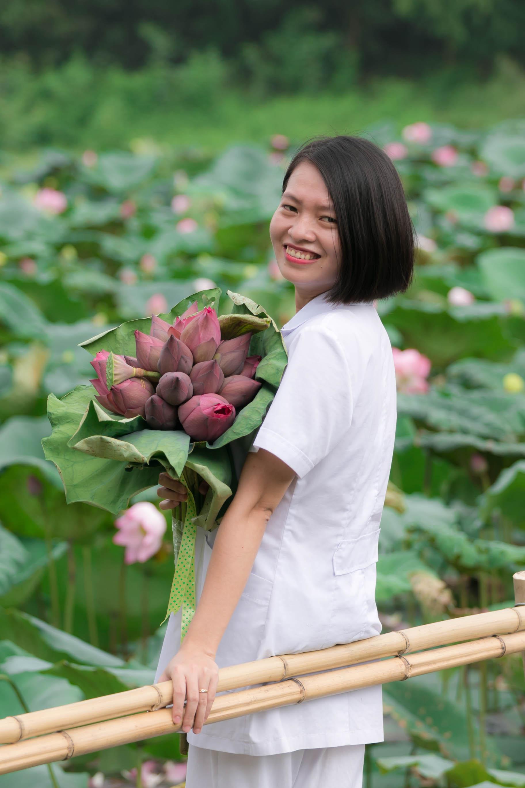 Chị Thiều Thị Hằng, cán bộ tổ Y tế, cũng tranh thủ chụp ảnh cùng bó hoa sen.