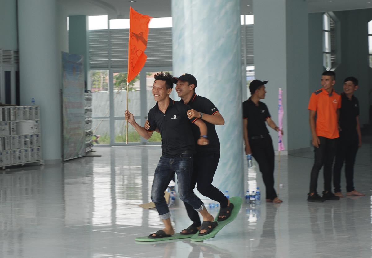 Ở trò chơi thứ 2, đội chia thành từng cặp thực hiện thử thách đi cặp dép dính liền trong thời gian ngắn nhất.