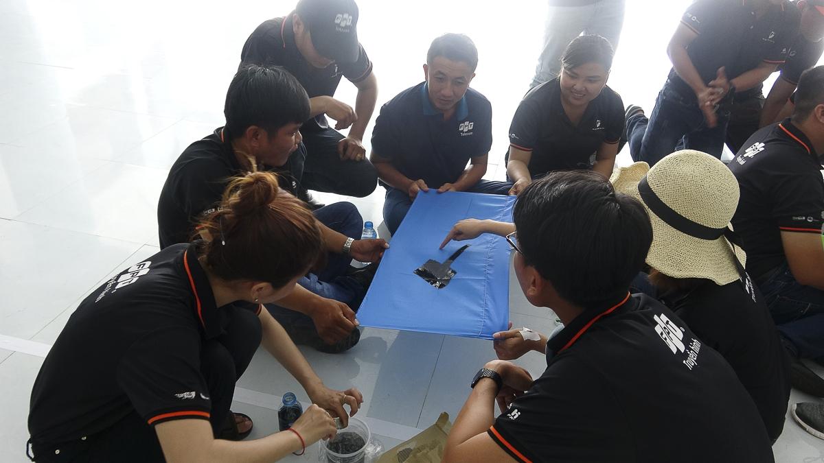 """Toàn thể người tham gia chia làm 6 tổ (mỗi tổ gồm các thành viên từ các chi nhánh khác nhau). Nhiệm vụ đầu tiên là sáng tạo tên đội với chữ """"Cá mập"""" và cờ đội với màu, cọ, băng keo.Với yêu cầu đặt ra là không để dính màu xuống sàn trong khi lá cờ khá mỏng, mỗi đội có một phương án riêng nhưchung tay giơ cờ lên cao hơn mặt sàn..."""