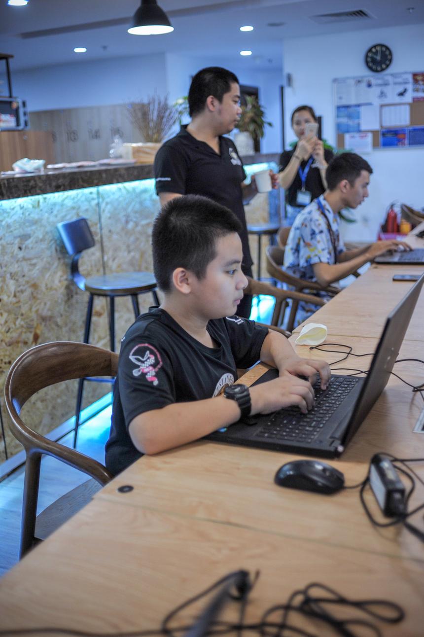 Không khí buổi thi diễn ra tập trung. Thí sinh đa dạng, trong đó có học sinh lớp 6 và sinh viên tự học lập trình tại nhà.