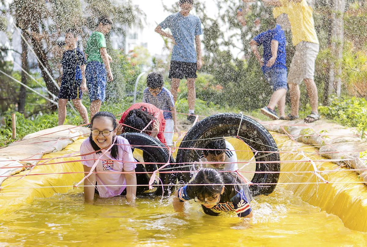 Các bạn nhỏ dầm mình dưới hố nước trong thử thách băng đồng. Dù vậy không bạn nào cảm thấy mệt mỏi, ngược lại đều tỏ ra rất vui tươi.