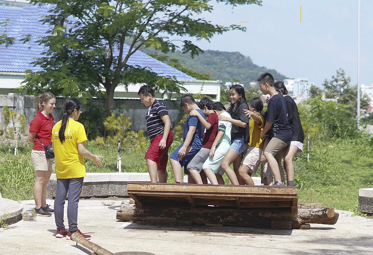 Thử thách bập bênh trên ván do cô giáo Alex đặt ra cho các bạn nhỏ với yêu cầu phải cùng nhau thực hiện sao cho không bạn nào rơi ra khỏi mặt gỗ.