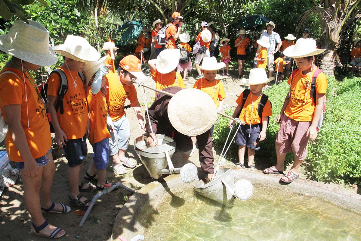 Sau khi trồng rau, bác nông dân bắt đầu công đoạn tưới nước. Một hồ nước bên cạnh nhanh chóng được phủ kín bởi những cái áo FPT Small.