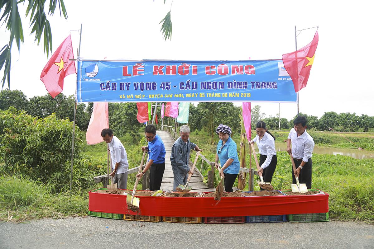 """Chú Trần Văn Bông (75 tuổi) chia sẻ đây là cây cầu dẫn thẳng vào vùng chuyên canh cây xoài Đài Loan của xã Mỹ Hiệp. Trước đây, cây cầu bằng gỗ với bề ngang chỉ 1m nên xe tải không thể vào thu mua trực tiếp: """"Giờ có Quỹ Hy vọng giúp đỡ mà ba con chúng tôi mừng không biết nói sao cho hết. Nhà ai trồng xoài cũng mong mỏi cây cầu này để thuận lợi hơn cho việc trồng trọt, mua bán""""."""