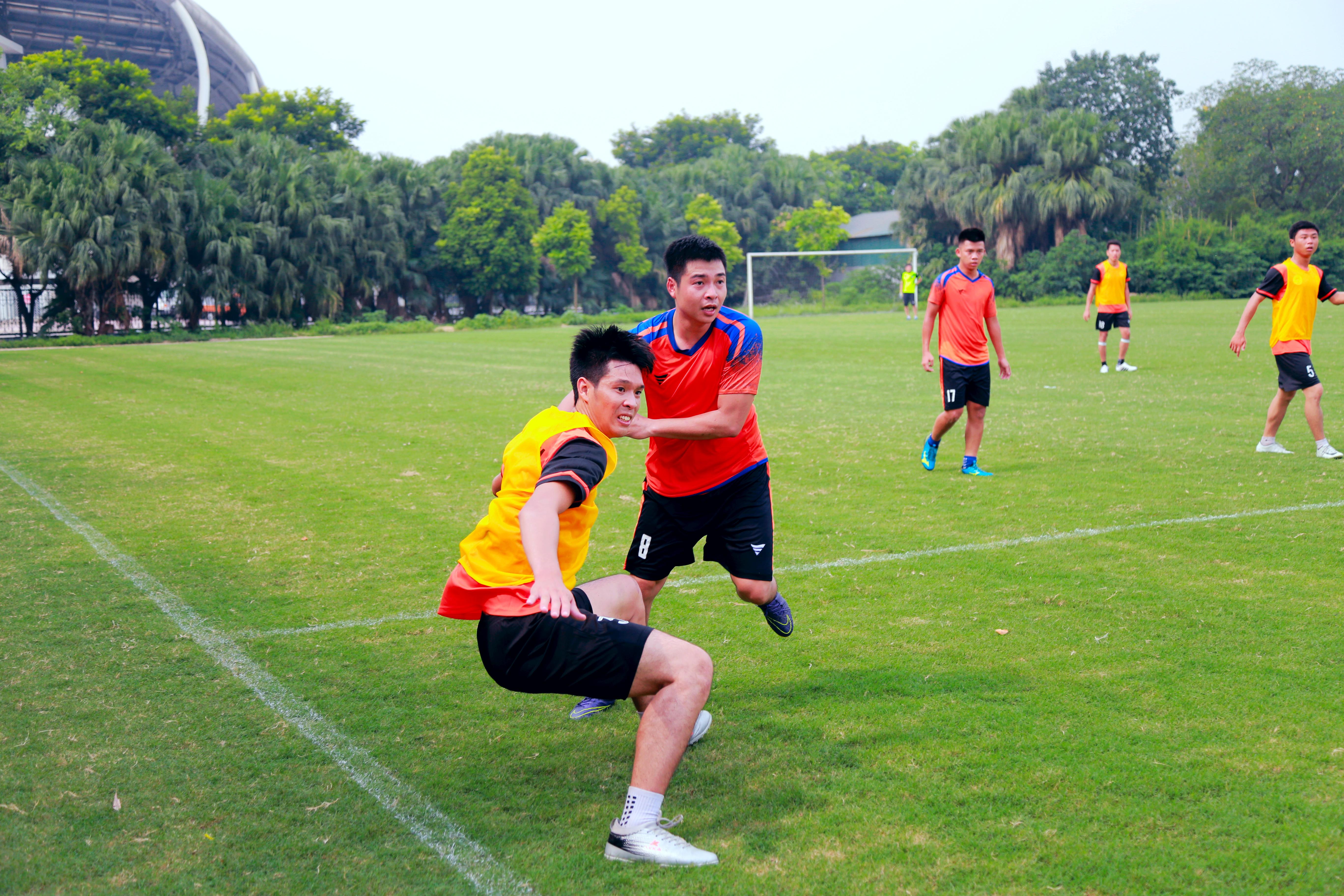 Giằng co: Hai cầu thủ giữa hai đội FPT Education và FPT Telecom đang giằng co nhau ở khu vực giữa sân để lấy bóng.