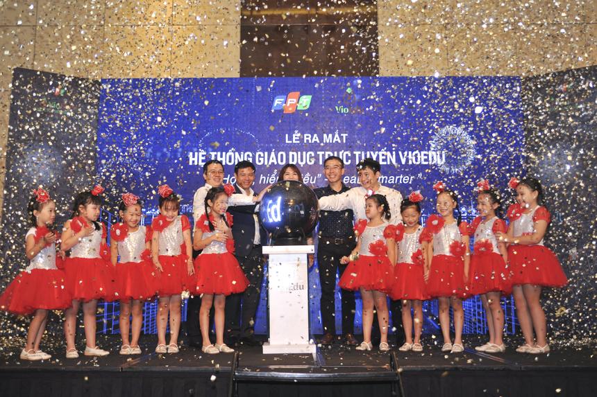 Lãnh đạo FPT và các em nhỏ đại diện cho thế hệ tương lai của đất nước cùng thực hiện nghi lễ nhấn chuông, chính thức ra mắt hệ thống VioEdu trên toàn quốc.