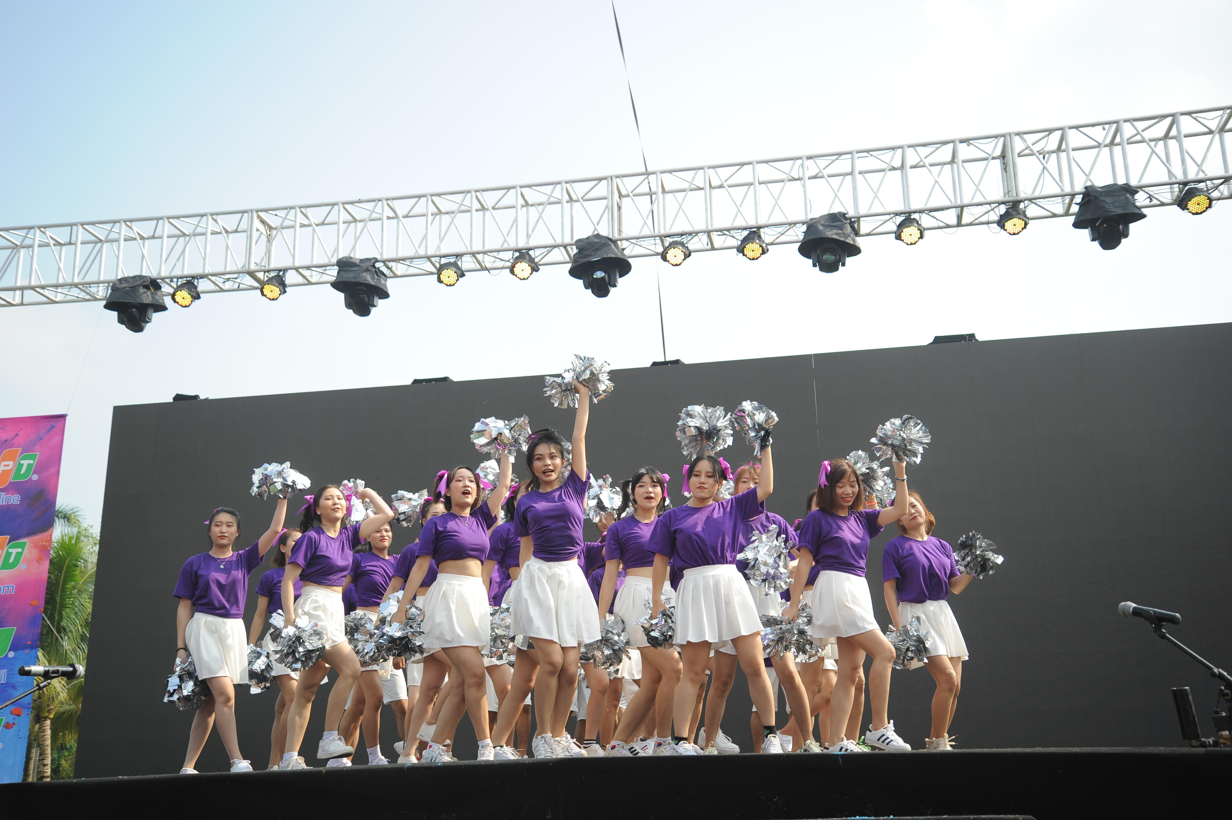 """Trong trang phục tím, bông cổ vũ bạc, FPT Education mang sự tươi trẻ, mộng mơ đến Hội thao FPT. Trên nền nhạc """"Đi đu đưa đi"""", các vũ công thể hiện nhiệt huyết này qua từng động tác tạo hình, vũ đạo."""