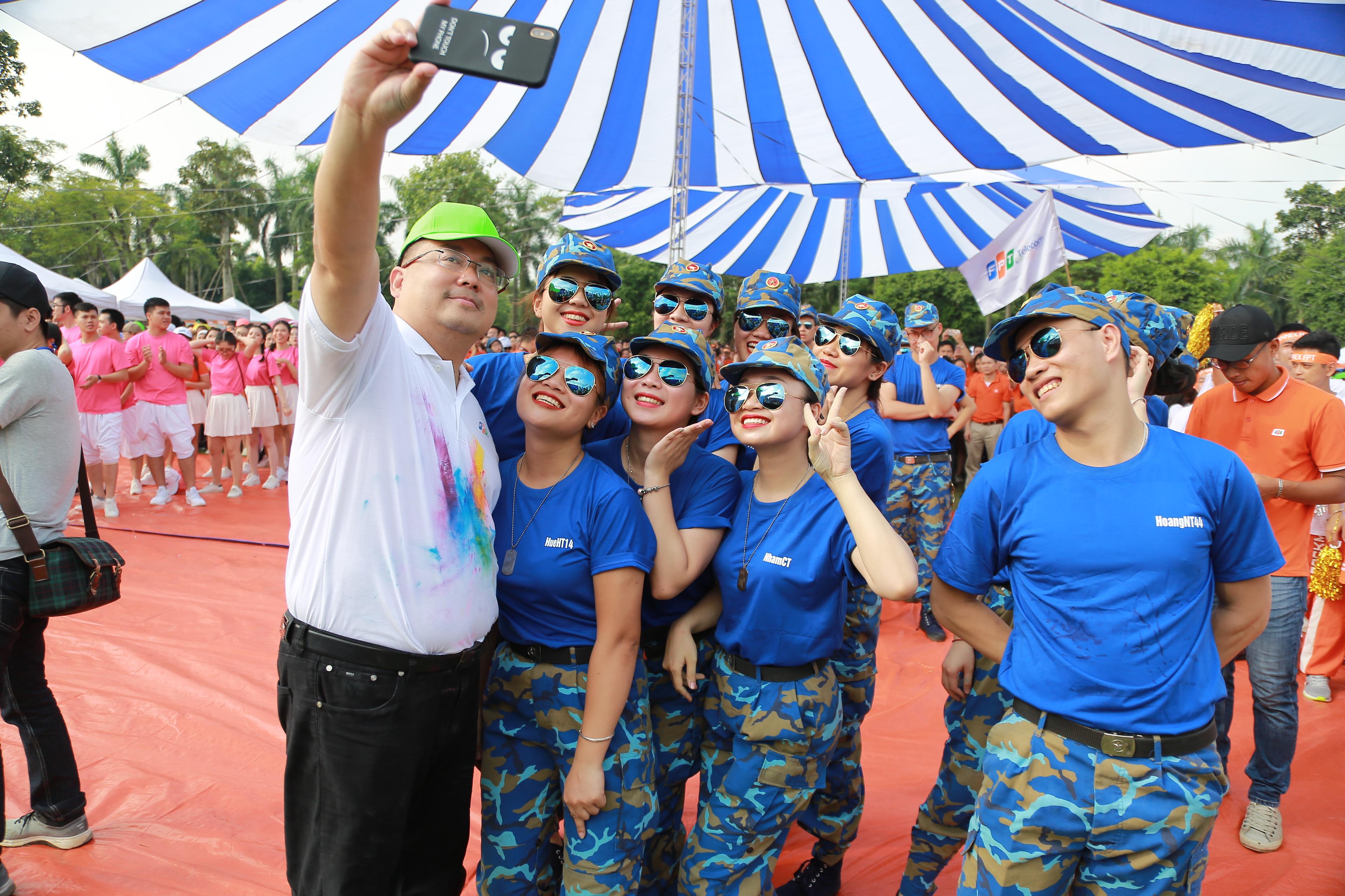 Anh Hoàng Nam Tiến đi đến từng đội đồng diễn của các công ty thành viên để chụp ảnh cùng đồng nghiệp.