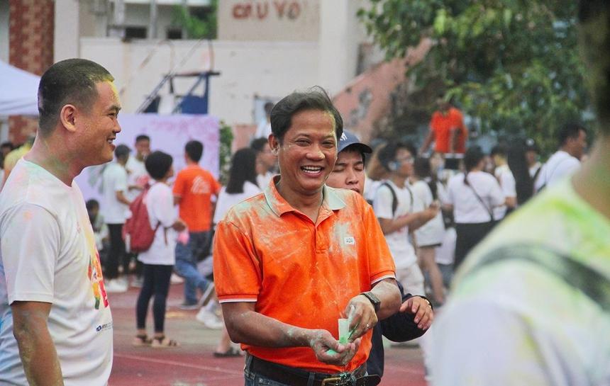 """Trưởng Ban tổ chức Nguyễn Minh Đức (áo cam) không ngận ngại """"tắm bột màu"""" cùng CBNV."""