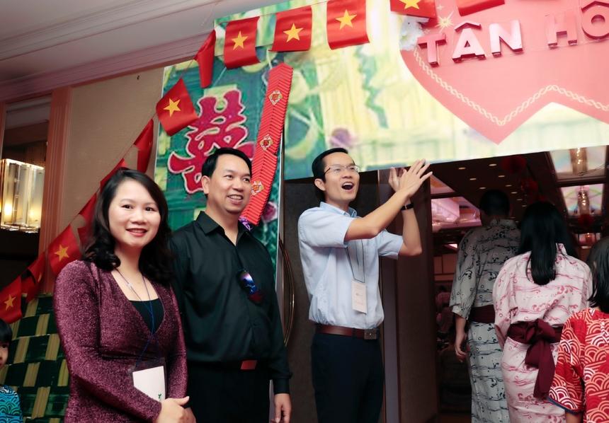 """Đám cưới tập thể FPT Japan diễn ra vào tối ngày 21/9, trong khuôn khổ chương trình nghỉ mát của công ty. 11 cặp đôi cùng tham gia một lễ cưới đặc biệt, khi chủ hôn là lãnh đạo và người dự cưới chính là đồng nghiệp. Không gian được bài trí tái hiện lại đám cưới những năm 90. Cổng chào đón khách với chữ hỉ đỏ thắm cùng cờ Việt Nam. Bên trong hội trường, BTC đã cắt dán lồng đèn, dây hoa giấy đỏ, ảnh 11 cặp đôi. Sân khấu chính với dòng chữ nổi bật """"Đám cưới tập thể - 20 năm thanh xuân"""" nổi bật trên khung nền đỏ."""
