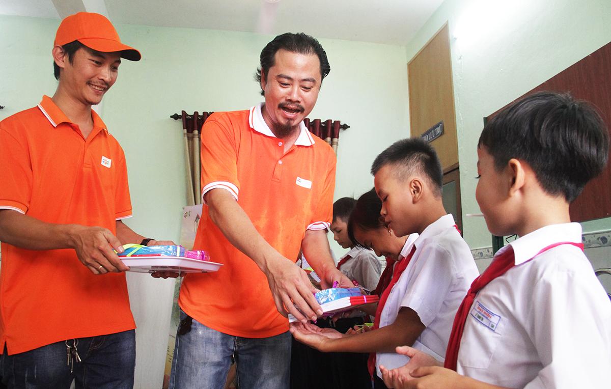 Đại diện đoàn FPT trao quà cho các em học sinh gồm 500 dụng cụ học tập và 500 phần quà bánh kẹo.