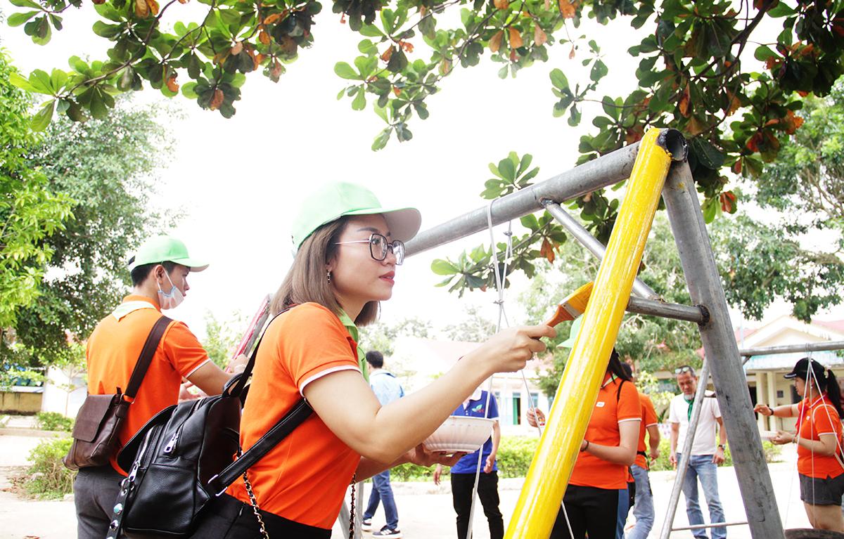 Một nhóm người FPT bắt tay vào công việc sơn khu vui chơi. Trước đó, khu vui của FPT đã được di chuyển đến điểm trường và cho tiến hành lắp ráp.