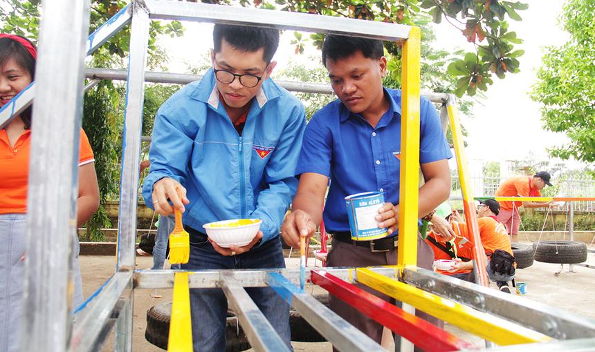 Để hoàn thiện khu vui chơi, người FPT phối hợp với đoàn xã cho sơn màu và vệ sinh trước khi cho các em học sinh sử dụng.