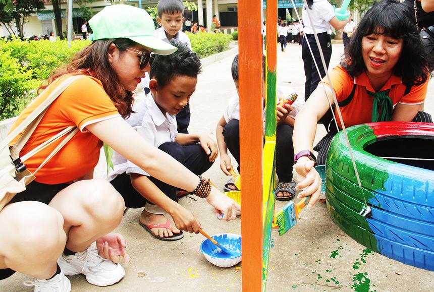 """Chị Trịnh Thu Hồng, Trưởng Ban đào tạo cán bộ FPT, tích cực tham gia sơn khu vui chơi. Trong quá trình làm, chị còn nhận được sự giúp đỡ của các em học sinh. """"Đây là chương trình ý nghĩa và có sức lan tỏa lớn, đặc biệt khi nó được tổ chức tại địa phương còn nhiều khó khăn như xã Đrây Sap"""", chị chia sẻ."""