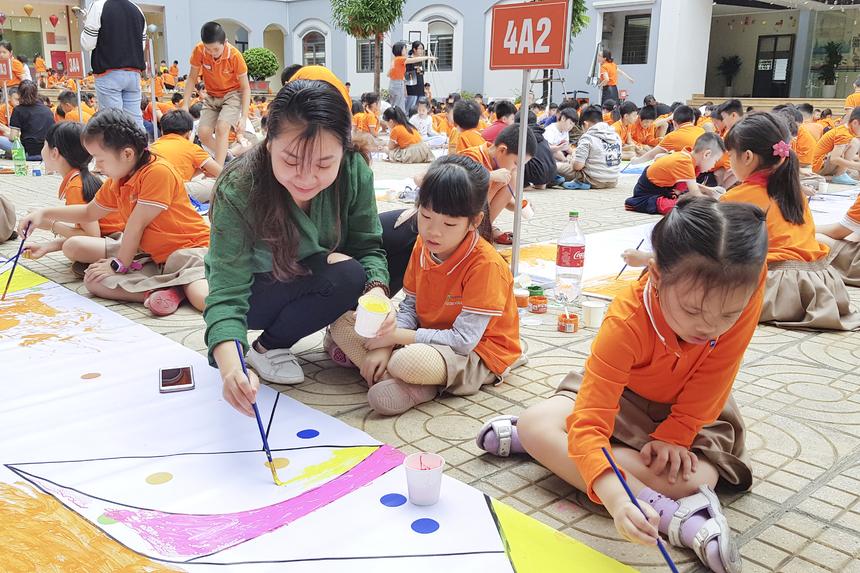 Chị Nguyễn Thu Hà - nhân viên hành chính FPT Schools cũng tham gia cùng các em để tạo nên bức tranh siêu to khổng lồ.