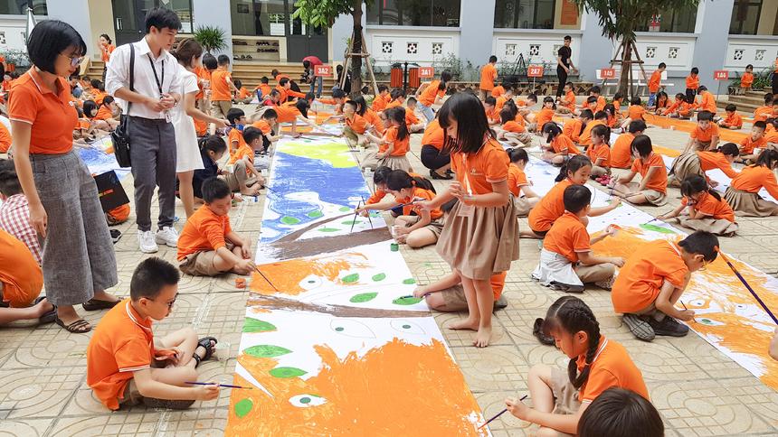 Phía giữa sân trường, các bạn chăm chú tô vẽ từng mảng màu một cách cẩn thận, tỉ mỉ nhất.