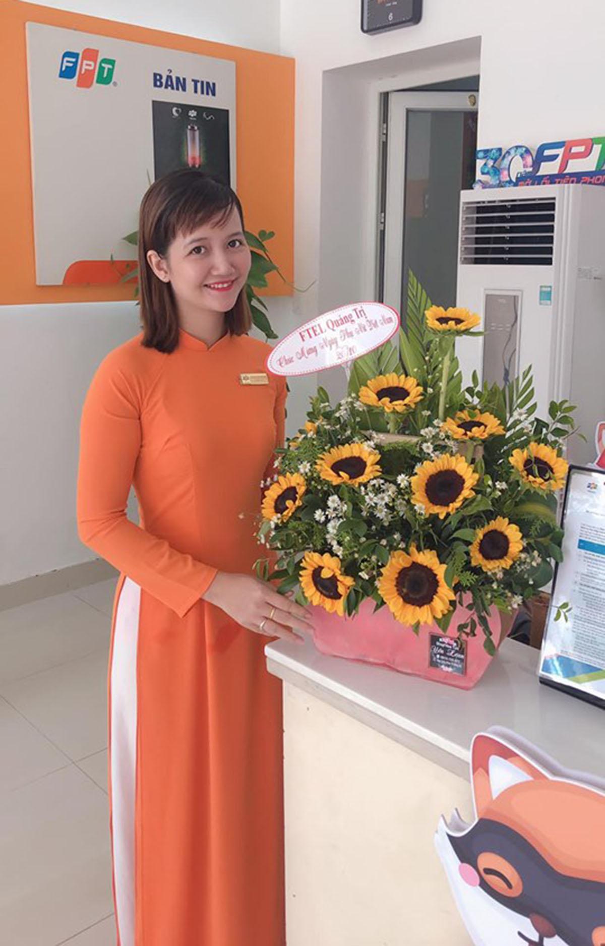 Nữ nhân viên Quảng Trị chụp hình lưu niệm cùng những đóa hoa tươi thắm do đồng nghiệp nam dành tặng.
