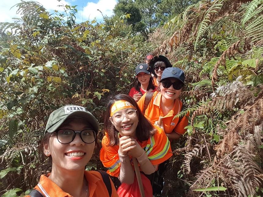 """Phạm Phương Thảo (ngoài cùng bên trái) - phòng công tác sinh viên ĐH FPT HN - chia sẻ về hành trình chinh phục Langbiang: """"Lần đầu Trekking Langbiang, có hơn hai nghìn mét chứ mấy. Lúc đầu thì nắng, nắng đẹp trong lành, gió hiu hiu thổi, vừa đi vừa quay clip chụp ảnh các thứ. Lên được 500m bắt đầu thở hồng hộc. Đúng như các lão bà leo núi tay run chân bủn rủn. Lên đến độ cao tầm hơn 1000m là lạnh và mưa, đoàn người lũ lượt kéo nhau đi lên rồi đi xuống. Khoảng 360m cuối cùng toàn dốc dựng đứng, người chặt như nêm, kế thêm là độ ẩm cao, leo lên mất sức vô đối. Lên đến đỉnh thì ôi thôi, toàn cam là cam""""."""