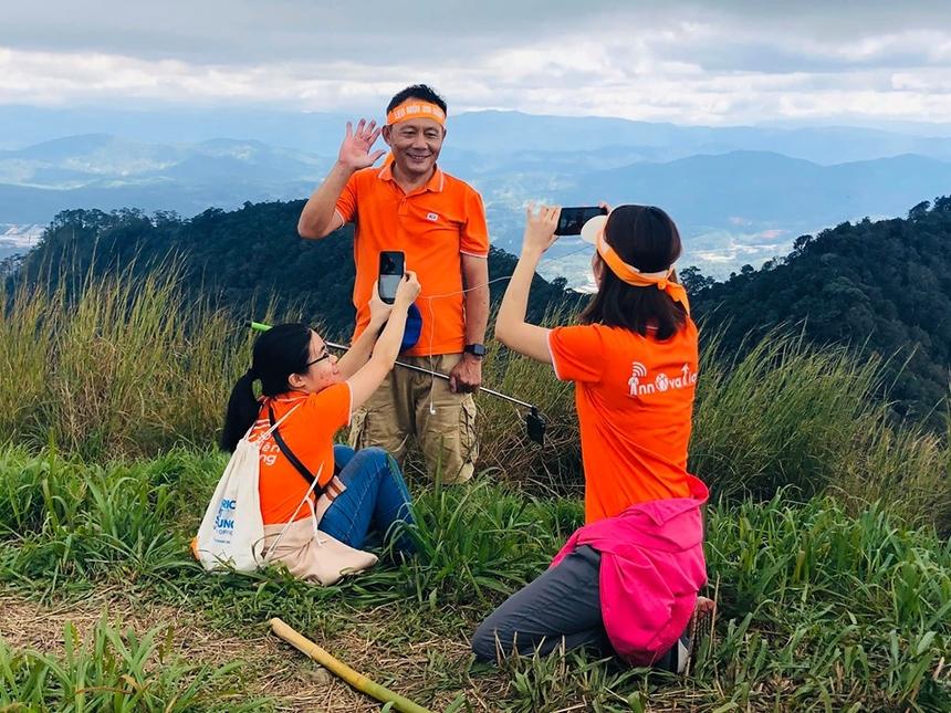 """Dù leo núi vất vả những vẫn không quên làm nhiệm vụ, đó là team truyền thông - PR. Chị Nguyễn Thị Thu Nga - Ban truyền thông FPT Education chia sẻ đây là lần đầu tiên tác nghiệp ở chốn cao và gần mây như thế: """"Đã hoàn thành hành trình 20 năm ngàn người FPT Edu lên đỉnh. Cùng đứng ở đỉnh 2.167m giữa nắng gió và cả mưa với hàng trăm đồng đội chung màu áo thật là xúc động ghê gớm. Lúc xuống, trời mưa đường khó đi. Có hàng chục bàn tay đồng đội giơ ra đỡ mình. Đó là khoảnh khắc khó quên của chặng đường lên đỉnh""""."""