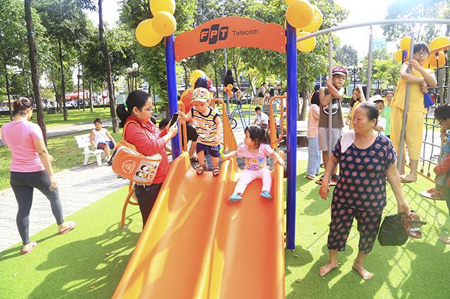 """""""Con rất thích được chơi ở đây"""", bé Quang Minh (4 tuổi) chia sẻ chơi cầu trượt. Công viên Làng Hoa là khu vực tập trung đông đảo người dân địa phương đến tập thể dục và vui chơi hằng ngày."""