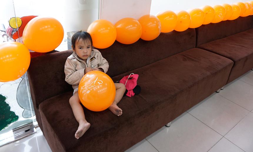 Một em bé thích thú với những quả bóng cam phủ kín thành ghế. Hình ảnh tại văn phòng giao dịch phường Bình Tân, TP HCM.