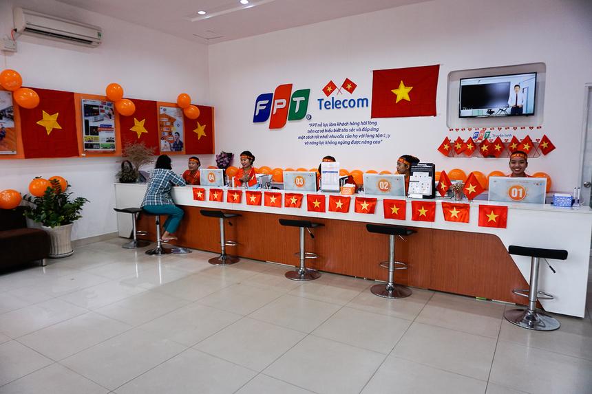 Cờ đỏ sao vàng nhuộm sắc quầy giao dịch cùng màu bóng cam, khiến không gian bừng sáng. Hình ảnh nhân viên chăm sóc khách hàng cũng trở nên thân thiện hơn với những chiếc băng-rôn cổ vũ như bao người hâm mộ bóng đá nước nhà.