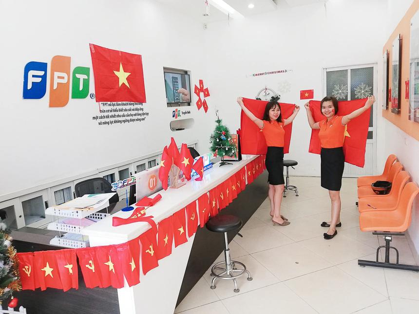 """FPT Telecom Điện Biênmột trong những chi nhánh trang trí cờ đỏ Việt nam đầu tiên. Chị Hứa Nhật Lệ - phòng giao dịch khách hàng hạnh phúc chia sẻ: """"Tháng 12 có lẽ là thời gian định mệnh cho đội tuyển Việt Nam. Chúng ta liên tiếp giành được nhiều thắng lợi trong bóng đá. Thật tự hào! FPT Telecom cũng tự hào về điều đó"""". Ảnh: ĐVCC."""