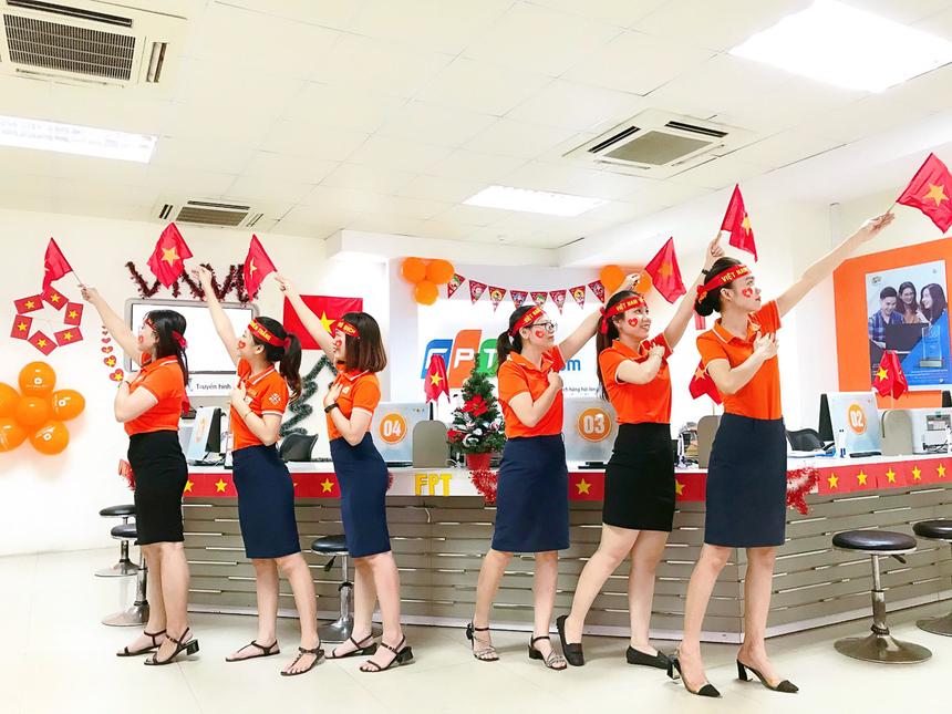 Nhân viên chăm sóc khách hàng FPT Telecom Khánh Hòa hân hoan niềm vui chung của cả nước.Chị Nguyễn Thị Nhân, cán bộ nhân sự FPT Telecom Khánh Hòa, cho biết chi nhánh đã cấp tốc trang trí vào sáng nay để ăn mừng cho đội tuyển Việt Nam, đặc biệt để khách hàng có những trải nghiệm thú vị khi đến quầy. Ảnh:ĐVCC.