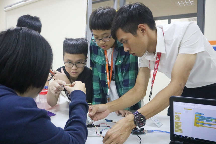 Smart Garden bắt đầu triển khai từ đầu tháng 11. Trước khi tiến hành lắp ráp các hệ mạch, học sinh đã được trang bị vững các kiến thức lý thuyết liên quan đến nông nghiệp như: phân bón, các loại sâu bệnh đối với cây trồng, các tác nhân ảnh hưởng đến sự phát triển của cây… và kiến thức cơ bản về lập trình: các khối lệnh cơ bản, cách sử dụng phần mềm mBlock, thao tác lập trình bật tắt đèn LED, lập trình cảm biến độ ẩm đất, nhận diện các loại linh kiện… Trong ảnh: Thầy Vũ Như Huynh - giáo viên môn Công nghệ 4.0 hướng dẫn học sinh lắp ráp mạch - công đoạn khó, phức tạp và quan trọng nhất của dự án.