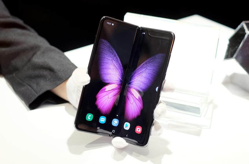 """Samsung Galaxy Fold thắng giải điện thoại xuất sắc nhất với 8,92 điểm, vượt qua iPhone 11 Pro Max và Oppo Reno 10x.Galaxy Fold trình làng tại MWC 2019, chính thức đến tay người dùng Việt Nam từ tháng 12, giá 50 triệu đồng. Mẫu di động màn hình gập của Samsung được đánh giá cao bởi thiết kế sáng tạo, hiệu năng mạnh mẽ và trải nghiệm thân thiện với người dùng. Đây là smartphone đầu tiên mở đầu cho trào lưu smartphone màn hình OLED dẻo, giúp thiết bị """"biến hình"""" từ điện thoại nhỏ gọn 4,6 inch thành máy tính bảng 7,2 inch. Galaxy Fold cũng được trang bị cấu hình khủng với chip Snapdragon 855, RAM 12 GB, bộ nhớ trong 512 GB, tổng dung lượng pin lên đến 4.300 mAh. Máy được trang bị 6 camera với đầy đủ các tính năng chụp phong cảnh, chân dung, góc rộng."""