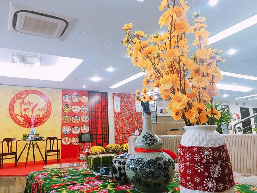 Sảnh FPT Massda, TP Đà Nẵng, được trang trí chủ đạo với hình ảnh hoa mai, hoa cúc cùng bánh chưng ngày Tết.