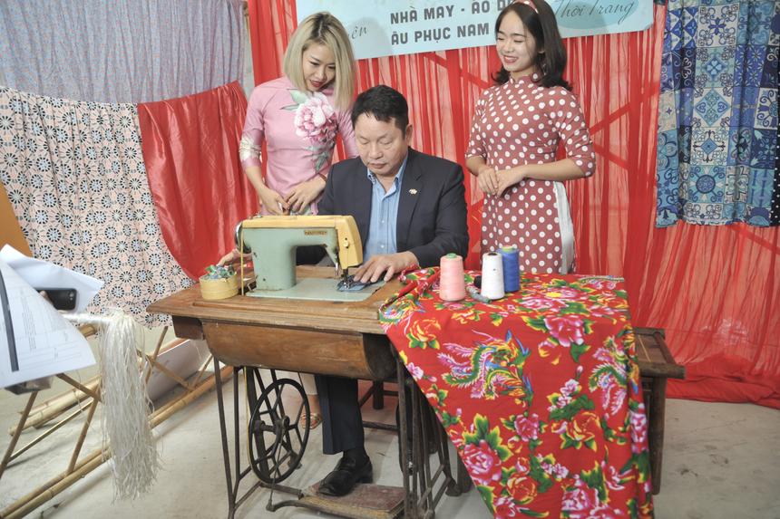 """Chủ tịch Trương Gia Bình """"thử sức"""" với một chiếc máy may cổ xưa của gian hàng nhà Giáo dục."""