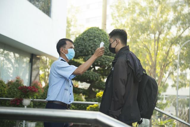 Người FPT tại Tân Thuận (TP HCM) tiến hành đo thân nhiệt. Ảnh: Hoài Vũ