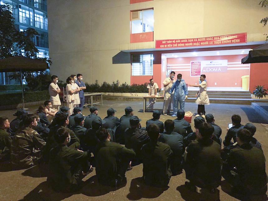 Các cán bộ y tế và lực lượng vũ trang được tập huấn cách thức sử dụng đồ bảo hộ trong quá trình tiếp xúc với người đến cách ly.