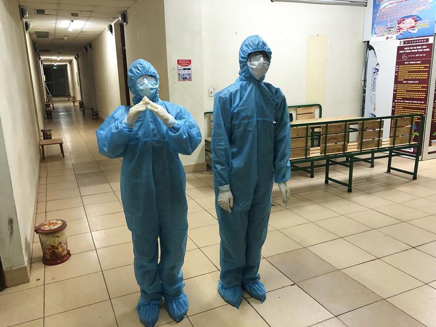 Các nhân viên y tế trong trang phục bảo hộ hướng dẫn người đến cách ly rửa tay và mang khẩu trang đúng cách.