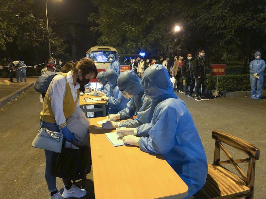 Người Việt về từ Trung Quốc, Hàn Quốc, Nhật Bản... làm thủ tục khai báo thông tin cá nhân tại bàn tiếp nhận.