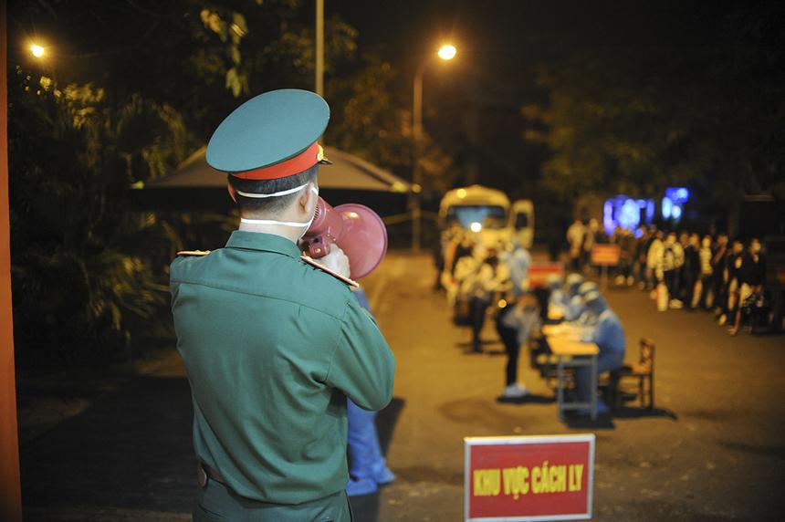 Đại diện Ban Chỉ huy quân sự huyện Thạch Thất (Hà Nội) dùng loa hướng dẫn người đến cách ly xếp hàng đúng quy định và phổ biến nội quy khu cách ly.