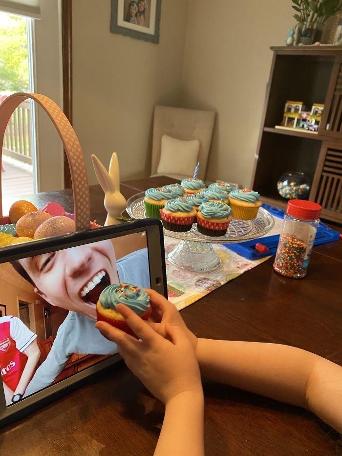 Con gái tôi cho em trai tôi ăn bánh cupcake trong bữa tiệc sinh nhật ảo.