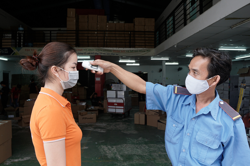 Trước khi vào kho làm việc, nhân viên phải được đo thân nhiệt, rửa tay diệt khuẩn.
