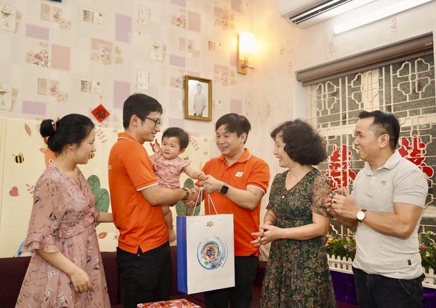 Anh Nguyễn Thượng Tường Minh (Phụ trách sản phẩm FPT.AI Platform) nhận quà tôn vinh từ tay anh Lê Hồng Việt (Giám đốc Công nghệ FPT) trong vòng tay của bố mẹ và vợ con.